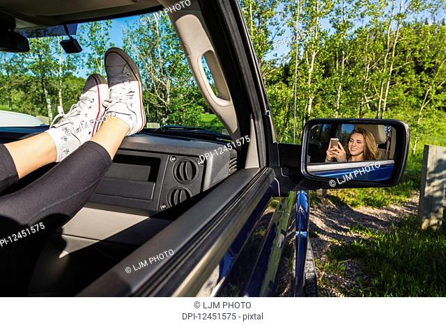 Young woman using her cell phone in a passenger seat in a vehicle; Edmonton, Alberta, Canada