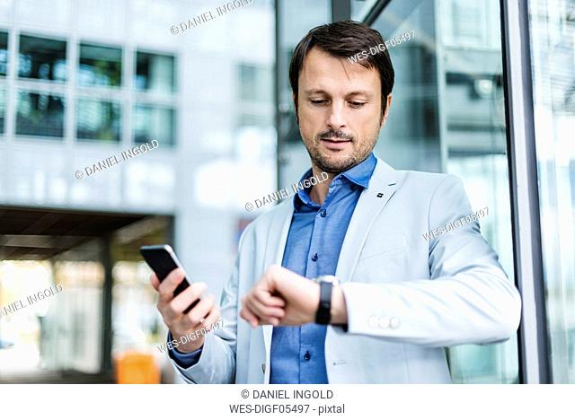 Portrait of a businessman checkin time, using smartphone