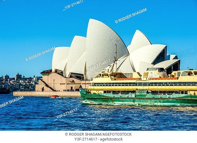 Sydney Opera House, NSW, Australia. A harbour ferry passes the building, leaving from Circular Quay