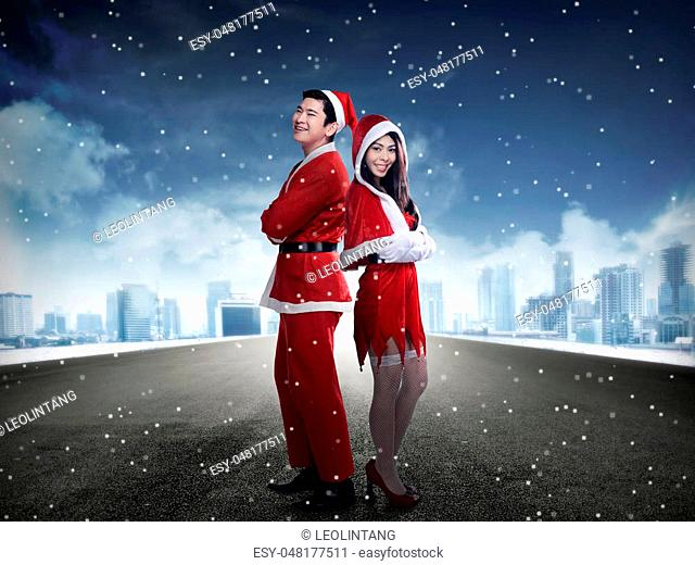 Happy couple in santa claus costume standing on the middle of the road. Christmas couple concept