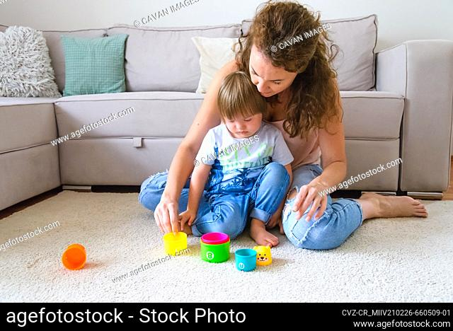 Single mother playing with disabled child with down syndrome