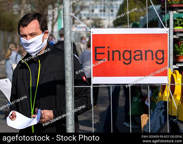 09 April 2020, Saxony, Dresden: An employee of the market management distributes masks at the entrance of a weekly market in the inner city