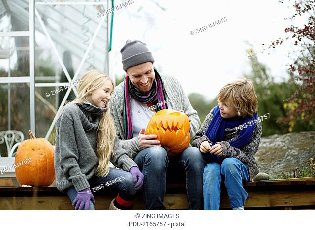 Father and children with pumpkins