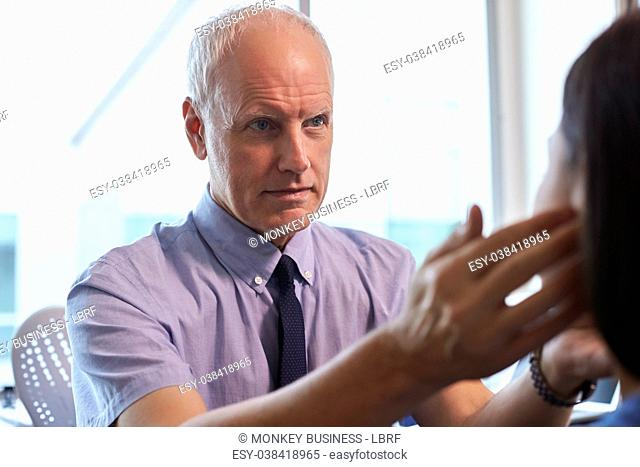Doctor Examining Female Patient In Office