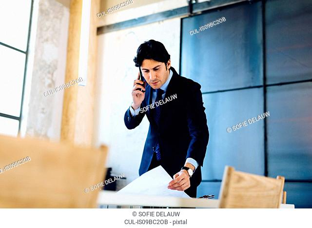 Businessman in office, using smartphone, looking through documents