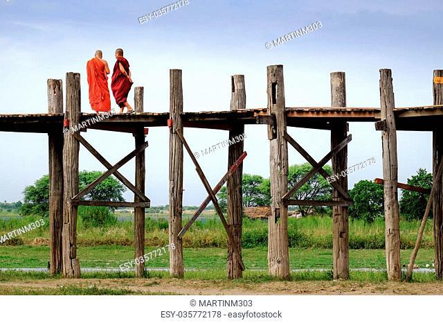 Amarapura, Myanmar - 28 June, 2015: Two monks in colorful robes walk on wooden bridge, Amarapura, Mandalay, Myanmar