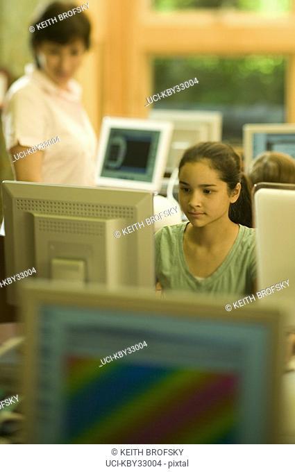 Teenage girl using computer with teacher
