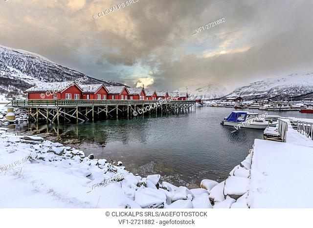Typical red wooden huts of fishermen in the snowy and icy landscape of Lyngen Alps Tromsø Lapland Norway Europe
