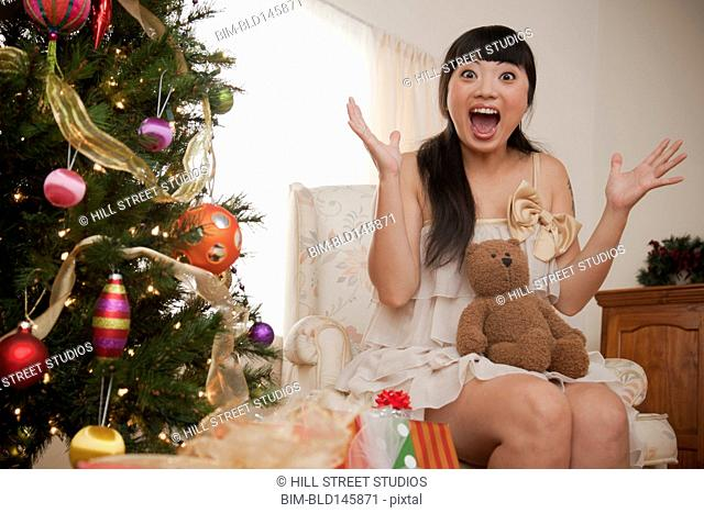 Excited Asian woman holding Christmas teddy bear