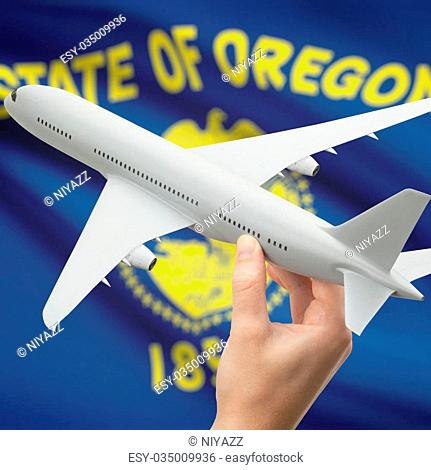 Airplane in hand with local US state flag on background - Oregon