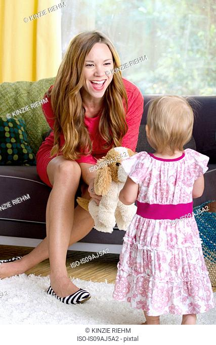 Mid adult mother playing with baby daughter and soft toy dog