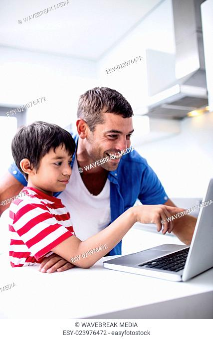 Father and son using laptop in kitchen
