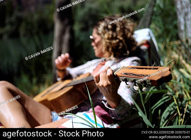 Woman with sunglasses playing guitar lying on a hammock