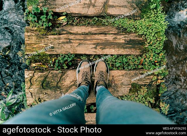 Point of view shot of woman standing on boardwalk above a brook on Sao Miguel Island, Azores, Portugal