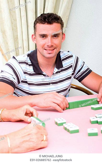 a young man smiling while playing mahjong with his friends