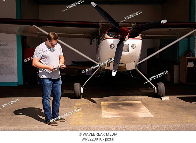 Man using digital tablet at hangar