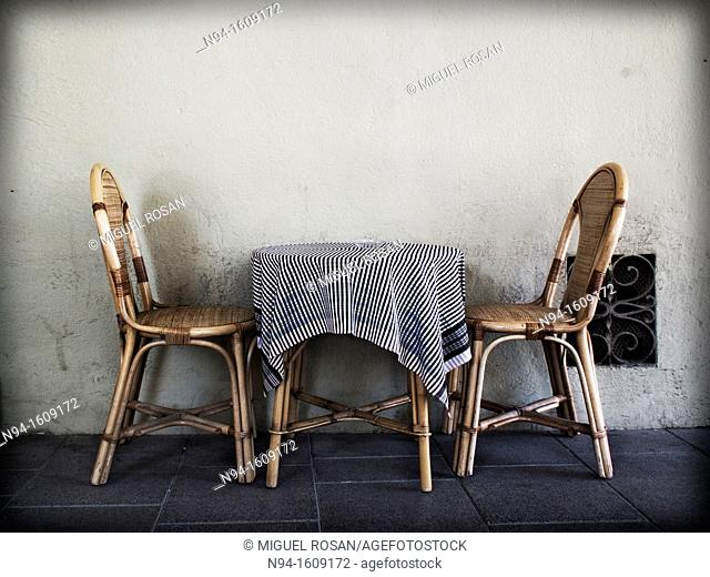 Two wicker chairs with a table and tablecloth on the terrace of a bar