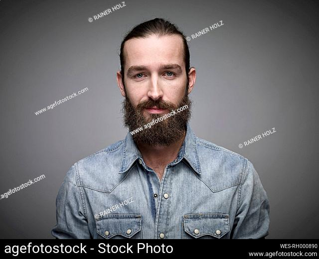 Portrait of man with full beard wearing jeans shirt