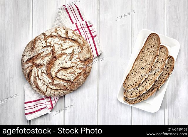 Loaf of rye bread and three slices on a white wooden background