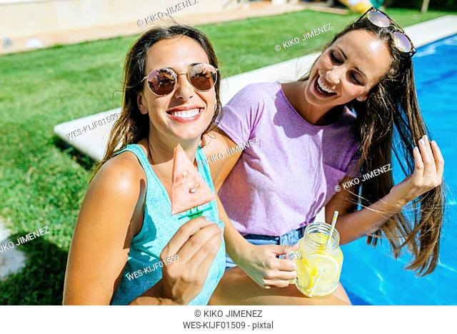 Two happy young women with drink and watermelon at the poolside