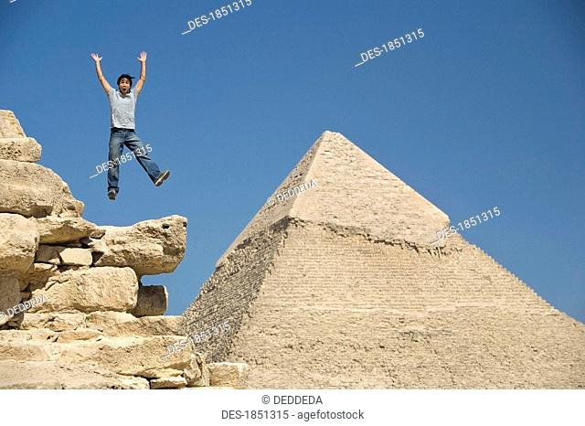Man jumping on part of a Pyramid in the desert