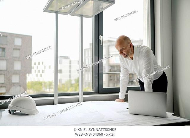 Engineer working in his office, using laptop
