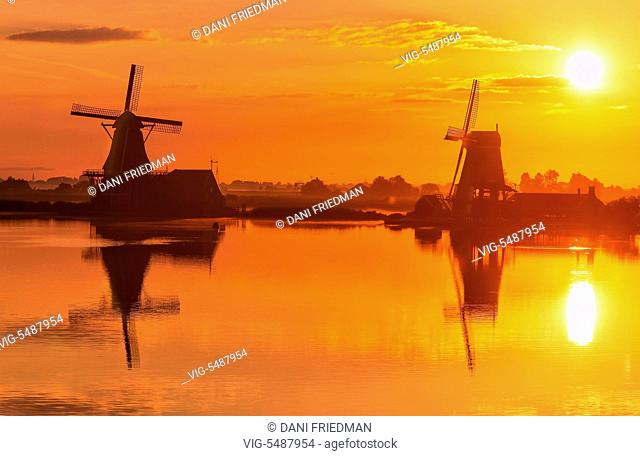 Windmills reflected in a canal during sunrise in the small town of Zaanse Schans, Holland, Netherlands, Europe. - ZAANSE SCHANS, HOLLAND, NETHERLANDS
