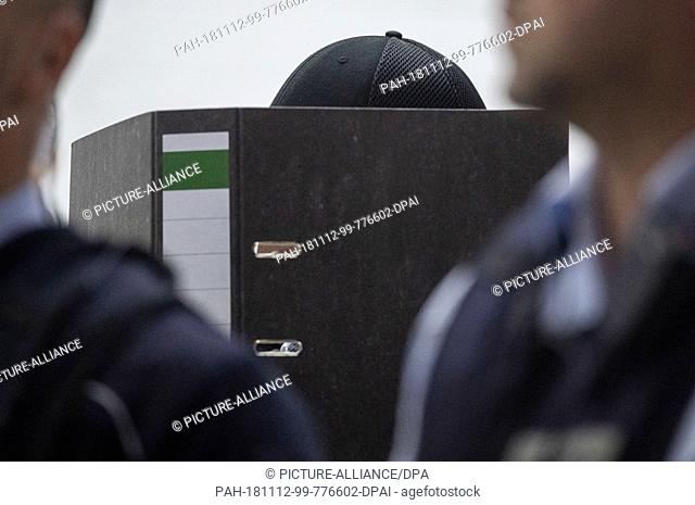 12 November 2018, Baden-Wuerttemberg, Stuttgart: A suspected Islamist (m) is holding a folder in front of his face in the courtroom of the Higher Regional Court...