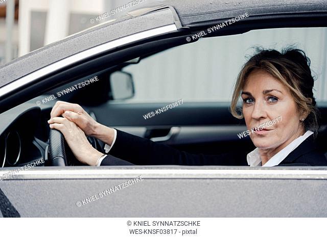 Portrait of confident senior businesswoman in car
