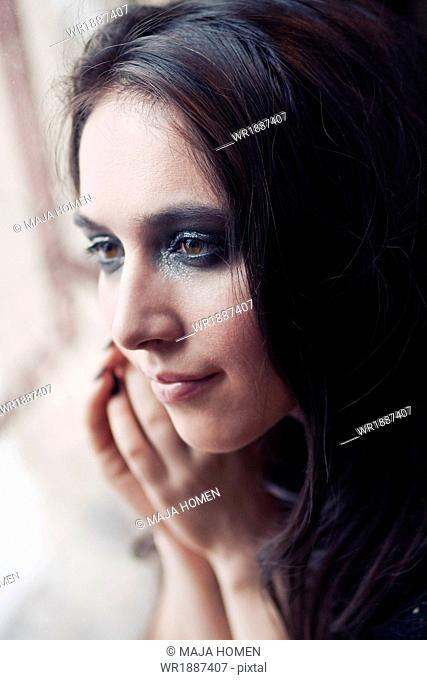 Young woman with long hair looking through window, Zagreb, Croatia, Europe
