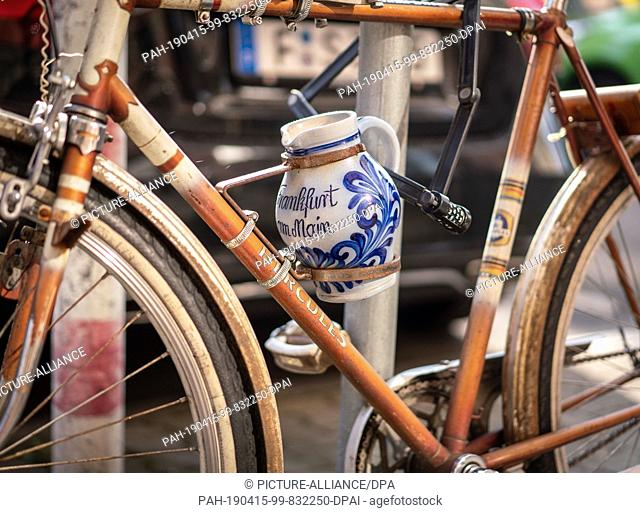 15 April 2019, Hessen, Frankfurt/Main: The owner of this bicycle, which is attached to a traffic sign and carries a pitcher in its drink holder