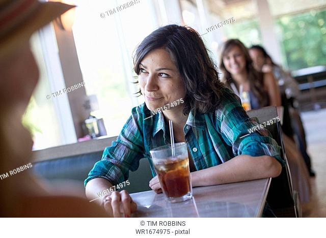A woman seated at a diner looking out of the window. A long cool drink with a straw