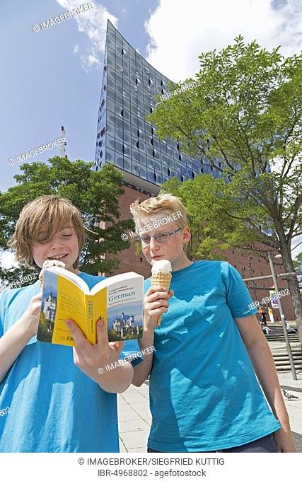 Young people on a language trip study a dictionary in front of the Elbe Philharmonic Hall, Hamburg, Germany, Europe