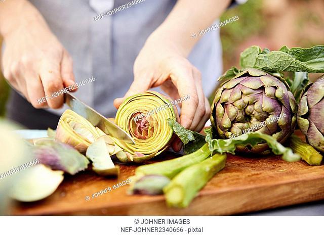 Person cutting fresh artichokes