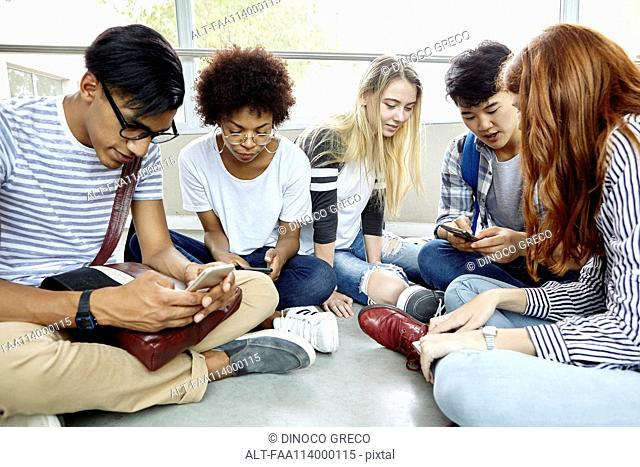 Students sitting together using smart phones