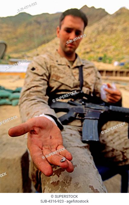 A US Marine Shows off a Piece of a Bullet Removed from His Wrist after a Firefight