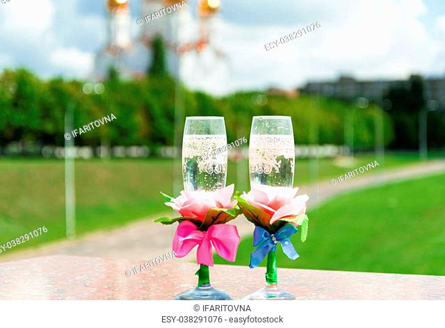 Two glasses of champagne on the stone railing on the background of the church