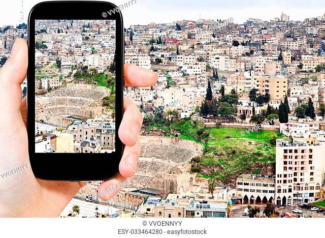 travel concept - tourist taking photo of Amman city on mobile gadget, Jordan