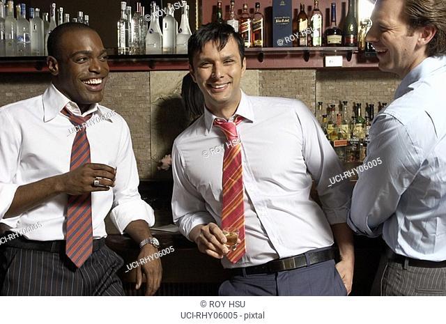 Three businessmen at bar talking