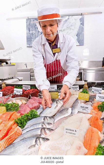 Female Fishmonger In Fresh Fish Department Of Supermarket