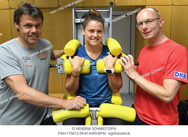 Ski jumping Olympic Champion Carina Vogt sits inside a torso training device next to Soeren Mueller (R), head of the specialist group at the IAT and federal...