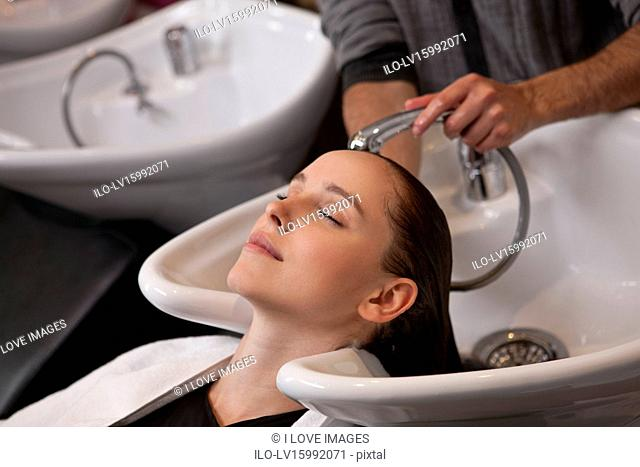A female client having her hair washed in a hairdressing salon, close up