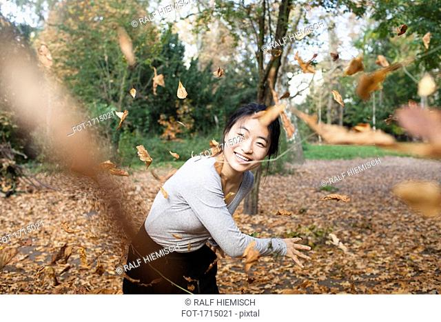 Portrait of happy woman throwing dry leaves in mid-air while standing at park during autumn