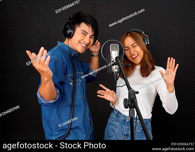 Young asian couples with headphones sing in chorus with microphone and pop filter on tripod stand. Musicians producing music in professional recording studio
