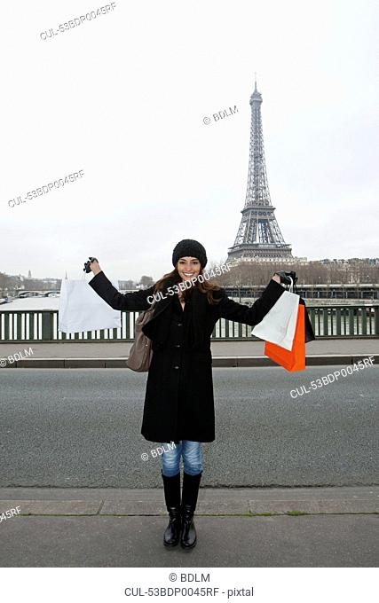 Woman with shopping bags by Eiffel Tower