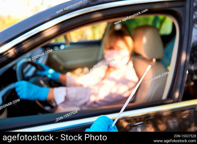 Rachen Abstrich Entnahme in Schnelltest Drive-In für Autofahrer während Coronavirus-Pandemie