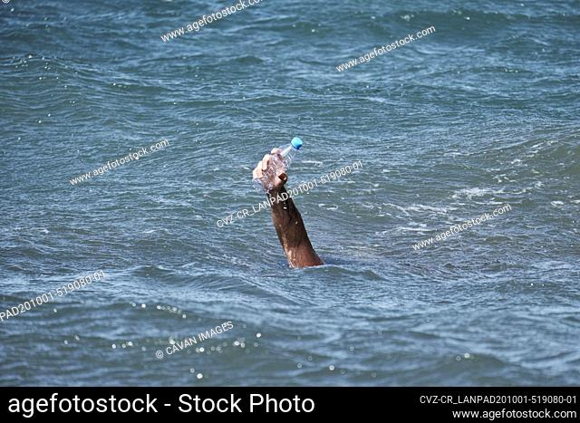 Man's hand holding plastic bottle waste in the ocean