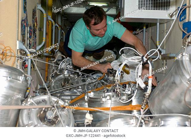 Cosmonaut Yury Lonchakov, Expedition 18 flight engineer, works with supplies and equipment stowed in the functional cargo block (FGB) or Zarya of the...