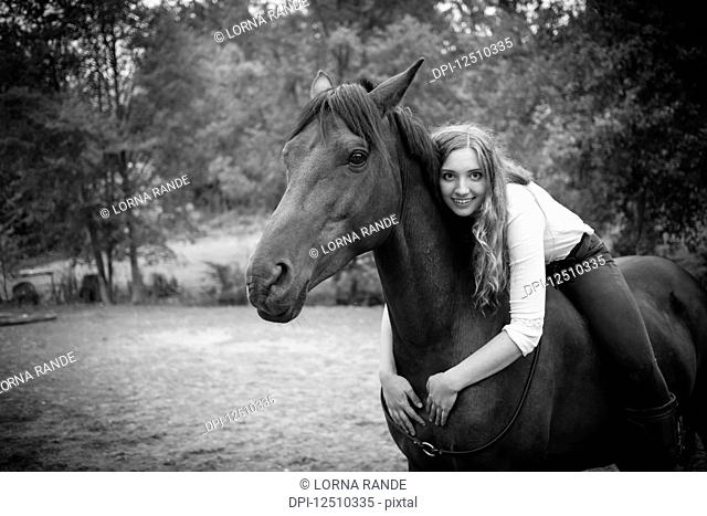 A young woman, a horse trainer and rider, sits and embraces her horse and poses for the camera; British Columbia, Canada