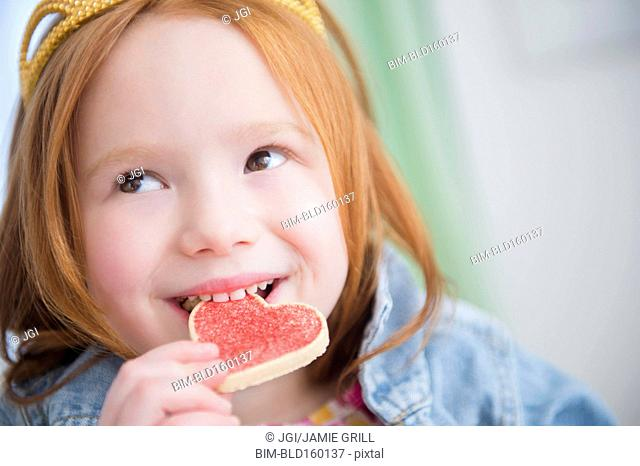 Caucasian girl eating heart-shape cookie